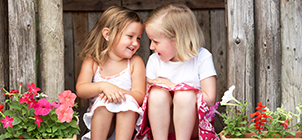 Featured  Photo: Two Young Girls Playing in Wooden House